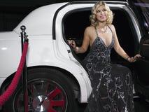 晚上穿戴离开的妇女大型高级轿车 免版税库存照片