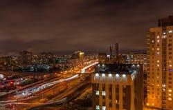 晚上都市风景 一个大都市住宅区和宽城市道路的看法 在前景的高大厦在右边 免版税库存照片