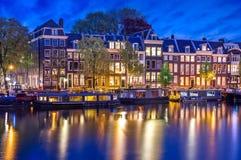 晚上镇阿姆斯特丹在银行的荷兰 免版税库存照片