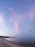 晚上阳光和云杉的树在海岸、桃红色云彩和蓝天背景 海滩海岸线展望期山夏天 免版税库存照片