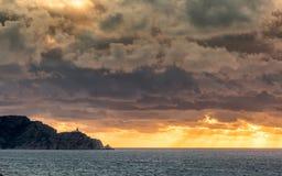 晚上阳光通过风雨如磐的天空在科西破裂了在Revellata 库存照片
