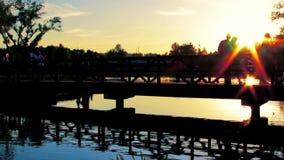 晚上风景和日落 人们沿河上的桥走在公园 股票视频