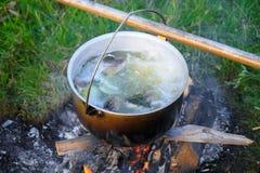 晚上鱼汤在一个营火的一顶圆顶硬礼帽在successfu以后 库存图片