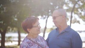 晚年、爱和人概念-在室外的爱的愉快的年长夫妇 愉快的年长前辈夫妇在晴朗的庭院里 股票视频