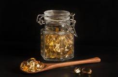 晚樱草胶囊在一个玻璃瓶子和在一把木匙子 免版税图库摄影