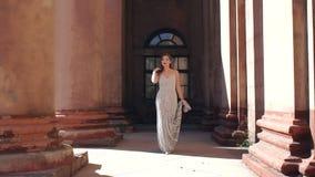 晚礼服步行的典雅的夫人以老豪宅为背景 股票录像