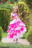 晚礼服的女孩在一个豪华的绿色庭院里 免版税库存照片
