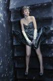 晚礼服的女孩在一架老梯子位于 免版税库存照片