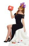 黑晚礼服的妇女和与礼物盒的狂欢节面具 坐白色毛皮 华伦泰假日和党概念 库存照片