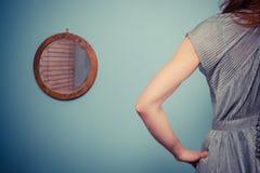 晚礼服的少妇在小镜子旁边 免版税库存照片