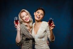晚礼服的微笑两个美丽的女孩,拿着酒杯 库存照片