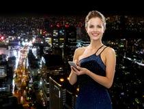 晚礼服的微笑的妇女与智能手机 库存照片