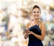 晚礼服的微笑的妇女与智能手机 免版税库存照片