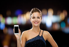 晚礼服的微笑的妇女与智能手机 免版税库存图片