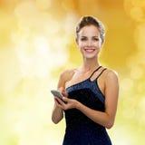 晚礼服的微笑的妇女与智能手机 图库摄影