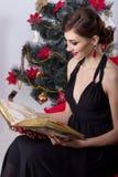 晚礼服的愉快的美丽的性感的妇女与构成和发型在与一本不可思议的书的一棵圣诞树附近坐在新的肯定 库存图片