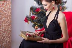 晚礼服的愉快的美丽的性感的妇女与构成和发型在与一本不可思议的书的一棵圣诞树附近坐在新的肯定 免版税库存照片