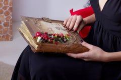 晚礼服的愉快的美丽的性感的妇女与构成和发型在与一本不可思议的书的一棵圣诞树附近坐在新的肯定 库存照片