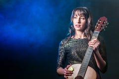 晚礼服的美丽的女孩与一把声学吉他在手上在发烟性背景 蓝色光 复制空间 库存照片