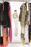 晚礼服的美丽的妇女有在前景的衣物路轨的 库存照片