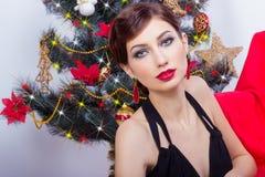 晚礼服的美丽的性感的愉快的微笑的少妇与与坐在圣诞树附近的红色唇膏的明亮的构成 库存照片