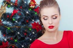 晚礼服的美丽的性感的愉快的微笑的少妇与与坐在圣诞树附近的红色唇膏的明亮的构成 免版税图库摄影