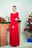 晚礼服的美丽的性感的愉快的微笑的少妇与与坐在圣诞树附近的红色唇膏的明亮的构成 免版税库存照片