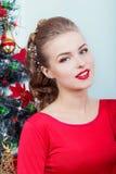 晚礼服的美丽的性感的愉快的微笑的少妇与与坐在圣诞树附近的红色唇膏的明亮的构成 库存图片