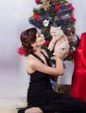 晚礼服的美丽的性感的愉快的微笑的少妇与与红色唇膏的明亮的构成,由圣诞树的开会 免版税图库摄影