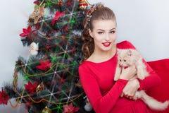 晚礼服的美丽的性感的愉快的微笑的少妇与与红色唇膏的明亮的构成,由圣诞树的开会 图库摄影