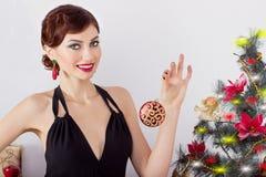 晚礼服的美丽的性感的愉快的微笑的少妇与与红色唇膏的明亮的构成,装饰一棵圣诞树 免版税库存图片