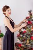 晚礼服的美丽的性感的愉快的微笑的少妇与与红色唇膏的明亮的构成,装饰一棵圣诞树 免版税图库摄影