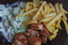 晚餐与chcken矿块、芯片和黄瓜沙拉 库存图片
