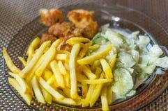 晚餐与chcken矿块、芯片和黄瓜沙拉 免版税库存照片