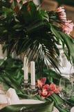 晚餐会的一张美丽的桌,装饰用兰花的棕榈树、白色蜡烛和花的叶子 免版税库存照片