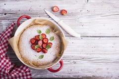 晚餐的家庭星期天蛋糕装饰用搽粉的糖、草莓切片和新鲜薄荷离开,蓬蒿 服务在a 库存图片
