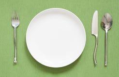 晚餐餐位餐具有银色叉子和匙子的一块白色板材 免版税库存图片