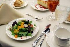 晚餐餐位餐具用沙拉、饮料和点心 免版税图库摄影