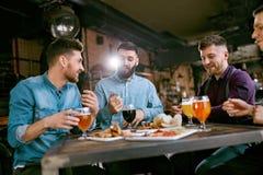 晚餐饮用的啤酒和吃食物的朋友在餐馆 免版税图库摄影