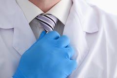 晨衣和衬衣的一位男性医生调整他的领带 免版税库存图片