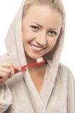 晨衣清洁牙的白肤金发的妇女有手工Toothbru的 免版税库存图片