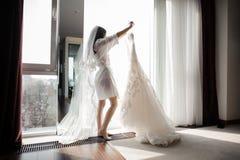 晨衣的拿着在挂衣架的新娘和面纱婚礼礼服 图库摄影