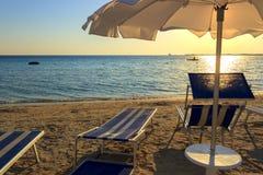 普利亚最美丽的沙滩  Salento海岸:在日落的伞 波尔图cesareo海滩 意大利(莱切) 库存图片
