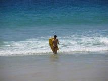 普吉岛泰国- 10 15 2012年:有冲浪板奔跑的女孩往波浪 免版税库存图片