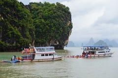 普吉岛,泰国- 2014年10月7日:两个游人船员皮船小船为旅客做准备在酸值洪Phang Nga海湾在普吉岛附近 图库摄影