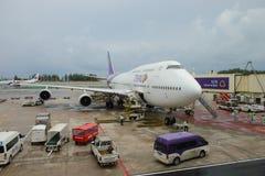 普吉岛,泰国- 2017年10月14日:泰航波音747-400 Reg HS-TGB地勤人员为下次飞行做准备向曼谷 免版税库存图片