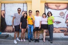 普吉岛,泰国- 2016年5月9日:艺术家亚历克斯面对,并且职员被拍了照片前面取消他墙壁上的艺术品 图库摄影