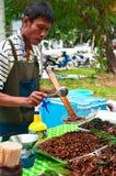 卖油煎的昆虫的泰国人在市场上 免版税库存照片