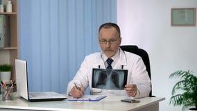 普尔独白者审查的患者X-射线,肺癌诊断,诊所服务 免版税库存照片