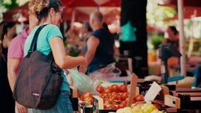 普拉,克罗地亚- 2017年8月4日 快乐的在地方农夫市场的妇女买的蕃茄 股票录像